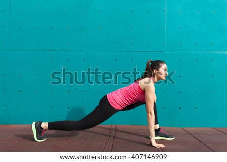 Beautiful young woman doing stretching exercises in front of turquoise wall - stock photo