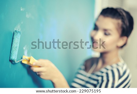 Beautiful young woman doing wall painting, standing - stock photo