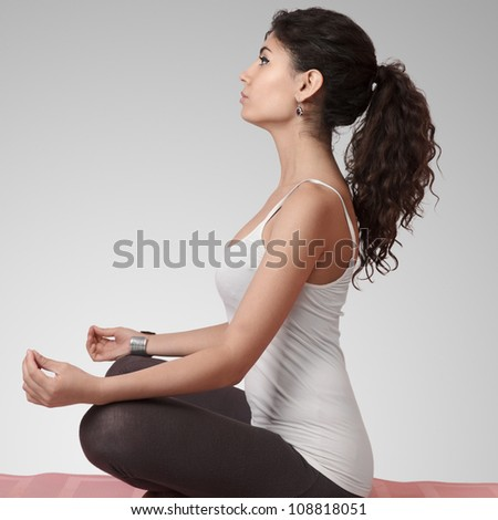 Beautiful young woman doing yoga exercise on mat - stock photo
