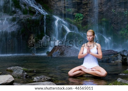 Beautiful young woman doing yoga in a water pool near waterfall