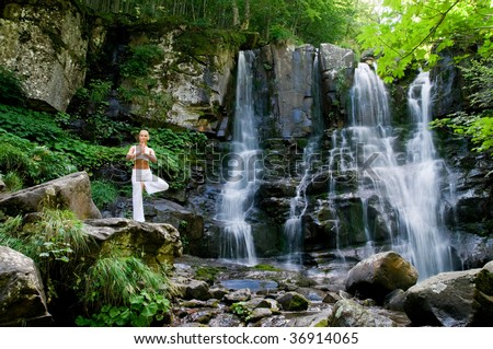 Beautiful young woman doing yoga in a wonderful forest near waterfall - stock photo