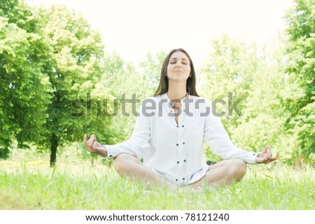 Beautiful young woman doing yoga in nature.