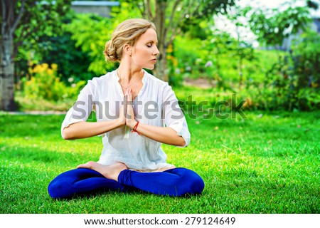 Beautiful young woman doing yoga in the summer park. Healthy lifestyle. Yoga. Lotus pose. - stock photo