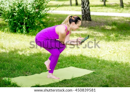 Beautiful young woman doing yoga in the summer park. Woman making yoga asana - eagle pose
