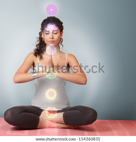 Beautiful young woman doing yoga meditation in lotus position with activated chakras over body - stock photo