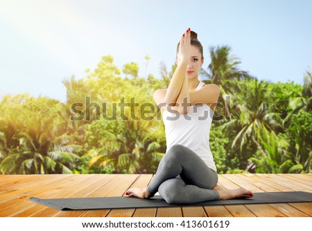 Beautiful young woman doing yoga on nature - stock photo