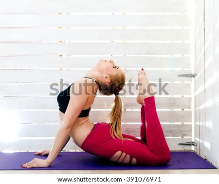 Beautiful young woman doing yoga. Wooden wall with light on the background.
