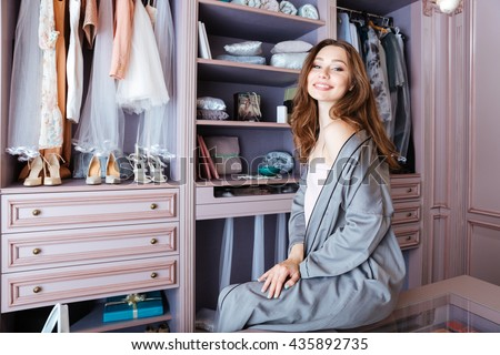 Beautiful young woman don't know what to wear sitting in her closet - stock photo