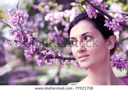 beautiful young woman dreaming outdoors with a lot of violet flower - stock photo