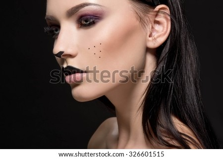 Beautiful young woman dressed as a cat. Make up cat. Halloween - stock photo