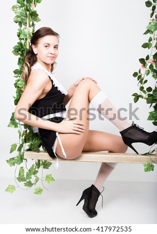 Beautiful young woman dressed as a sexy maid-servant in a skimpy uniform, posing provocatively and swinging on a swing - stock photo