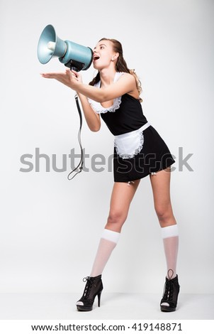Beautiful young woman dressed as a sexy maid-servant in a skimpy uniform, posing provocatively. she yells into a bullhorn. Public Relations - stock photo