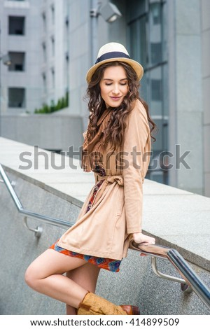 Beautiful young woman dressed in boho style. Girl on the background of the city. - stock photo