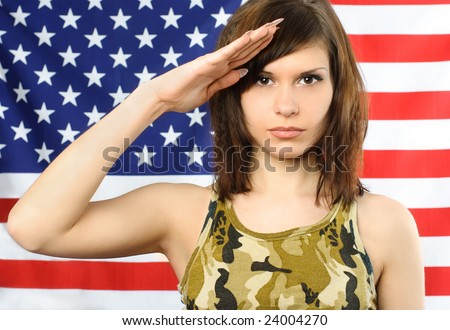 beautiful young woman dressed in camouflage stands near the American flag and salutes - stock photo