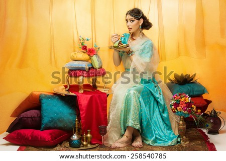 Beautiful young woman dressed in oriental style eating luxurious wedding cake - stock photo
