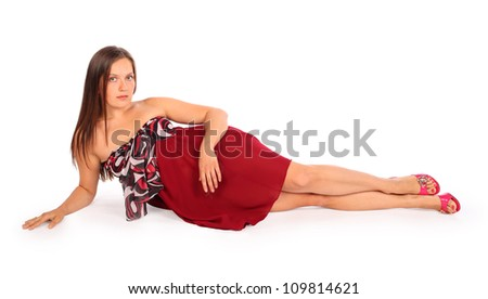 Beautiful young woman dressed in red pareo lies in studio on white background. - stock photo