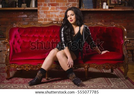 Beautiful young woman dressed in short lace dress posing  in a vintage interior