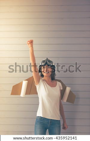 Beautiful young woman dressed like a pilot with toy wings is smiling and looking upward, standing against gray wall - stock photo