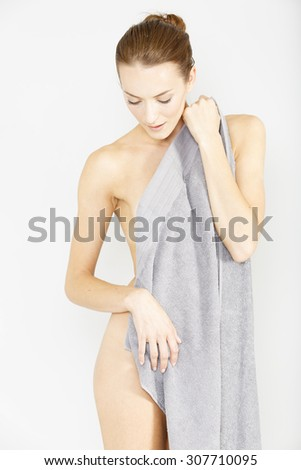 Beautiful young woman dressing at home naked with a towel draped over her