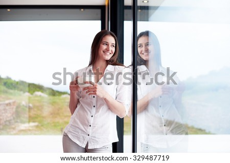 beautiful young woman drink first morning coffee at modern home interior with rain drops on big window door glass - stock photo