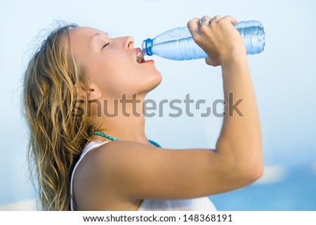 Beautiful young woman drinking a bottle of water in front of the sea