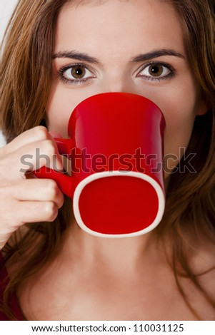 Beautiful young woman drinking a hot coffee, against a gray wall - stock photo