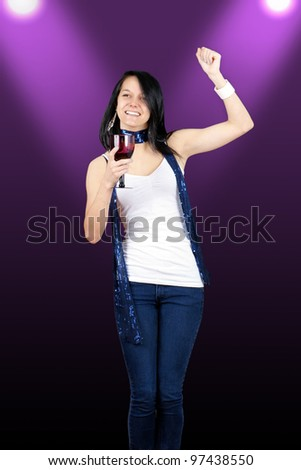 Beautiful young woman drinking and dancing at a disco club during a party.