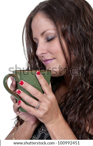 Beautiful young woman drinking and smelling coffee