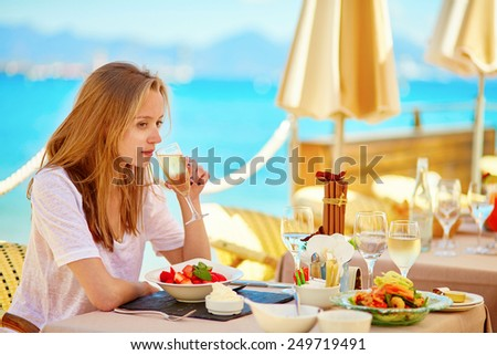 Beautiful young woman drinking champagne in a beach restaurant - stock photo