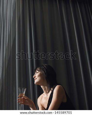 Beautiful young woman drinking champagne in front of curtains - stock photo