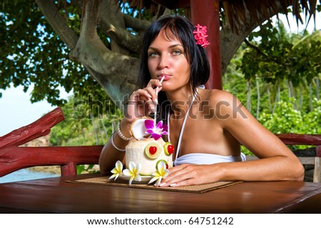 Beautiful young woman drinking cocktail outdoors - stock photo