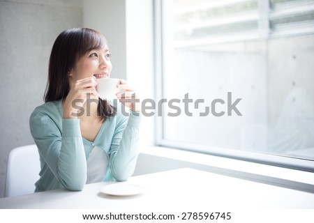 beautiful young woman drinking coffee - stock photo