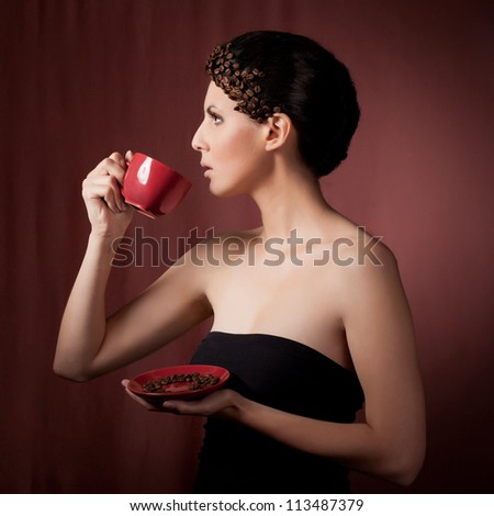 Beautiful young woman drinking coffee   against dark background. Concept of coffee - stock photo