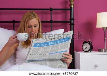 Beautiful young woman drinking coffee and reading newspaper - stock photo