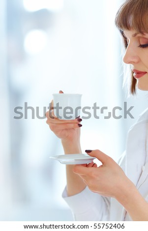 Beautiful young woman drinking fresh coffee,focus on the cup - stock photo