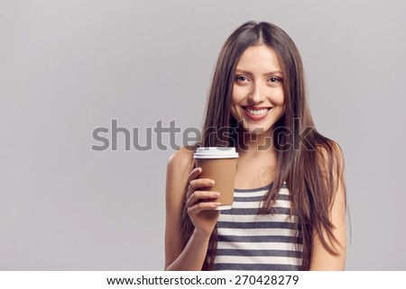 Beautiful young woman drinking hot drink from disposable paper cup, isolated over gray background, with copy space - stock photo
