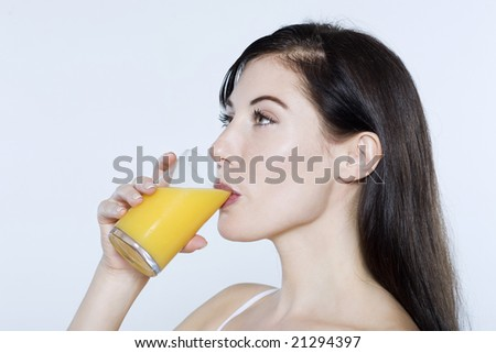 beautiful young woman drinking orange juice on isolated background