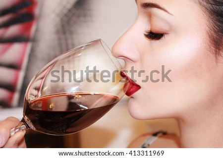 Beautiful young woman drinking red wine - stock photo
