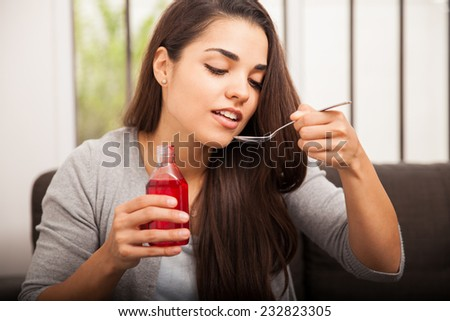 Beautiful young woman drinking some cough syrup from a spoon at home