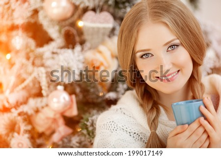 Beautiful young woman drinking tea at the Christmas tree. Beautiful girl celebrates Christmas with cup of cocoa. - stock photo