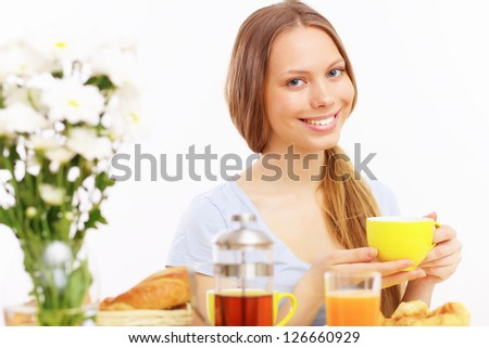 Beautiful young woman drinking tea from yellow cup - stock photo