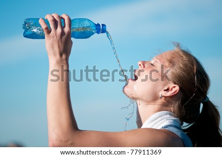 Beautiful young woman drinking water after exercise on sunny summer day - stock photo