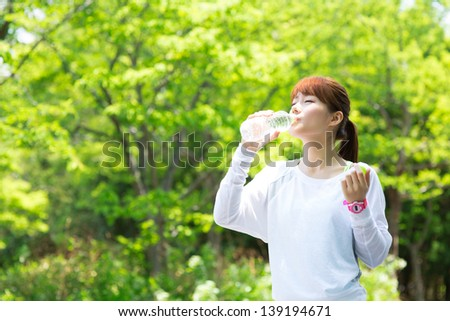 Beautiful young woman drinking water at workout - stock photo