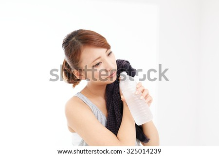 Beautiful young woman drinking water at workout. Portrait of asian. - stock photo