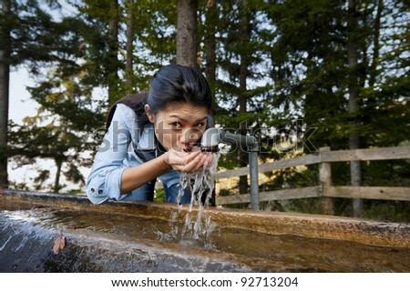 beautiful young woman drinking water from a well in the middle of a forest - stock photo