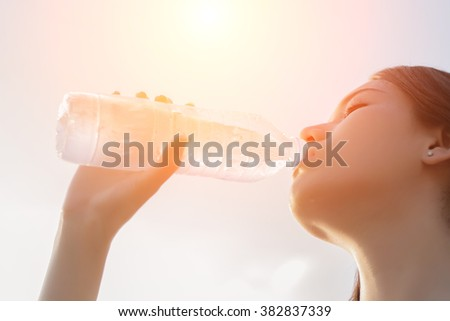 Beautiful young woman drinking water in the morning after finished jogging - stock photo