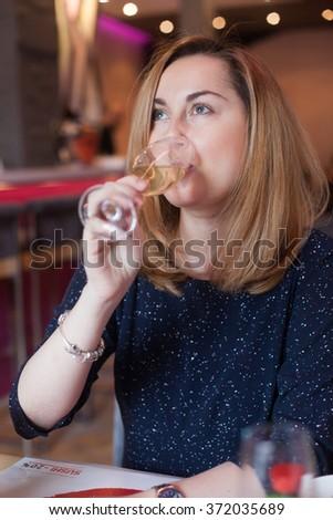 Beautiful young woman drinking wine - stock photo