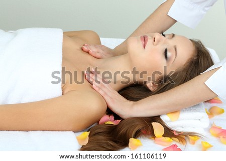 Beautiful young woman during massage in cosmetic salon close up