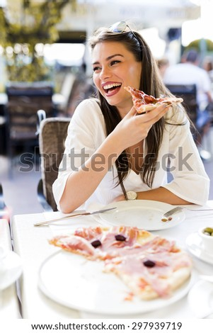 Beautiful young woman eating a slice of pizza in a restaurant  outdoors - stock photo