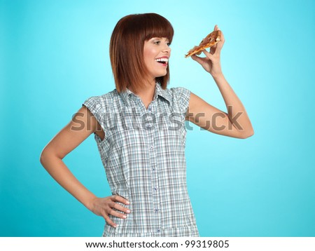 beautiful young woman, eating a slice of pizza, smiling, on blue background